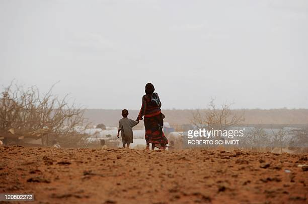 Haway Mohamed walks with her four year old son Noor toward the tent they now call home at the Kobe refugee camp near the EthiopiaSomalia border on...