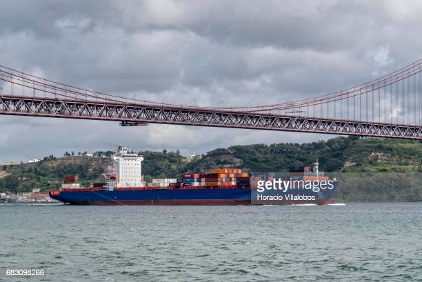 Hawk Hunter Container Ship sails by 25 de Abril bridge in the Tagus River on May 13 2017 in Lisbon Portugal Lisbon harbor is one of the largest and...