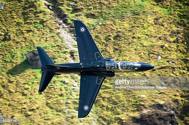 A Hawk jet trainer aircraft of the Royal Air Force low flying over North Wales.