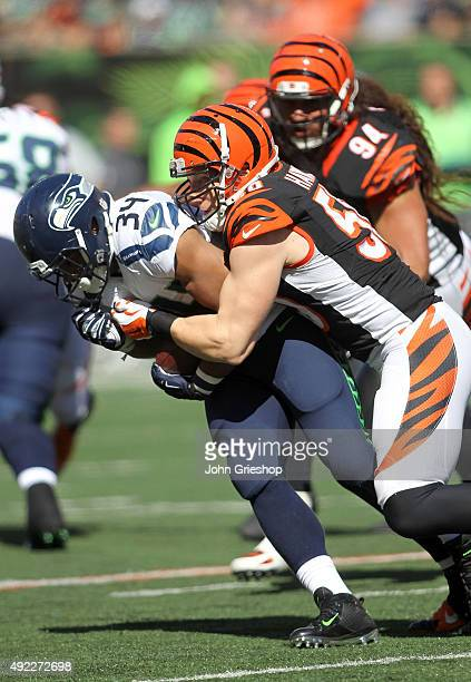 J Hawk of the Cincinnati Bengals tackles Thomas Rawls of the Seattle Seahawks during the second quarter at Paul Brown Stadium on October 11 2015 in...