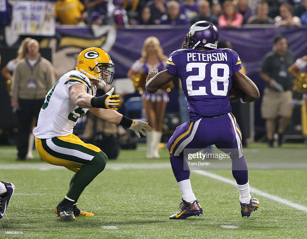 A.J. Hawk #50 of the Green Bay Packers tackles Adrian Peterson #28 of the Minnesota Vikings during an NFL game against the Minnesota Vikings at Mall of America Field at the Hubert H. Humphrey Metrodome on October 27, 2013 in Minneapolis, Minnesota.
