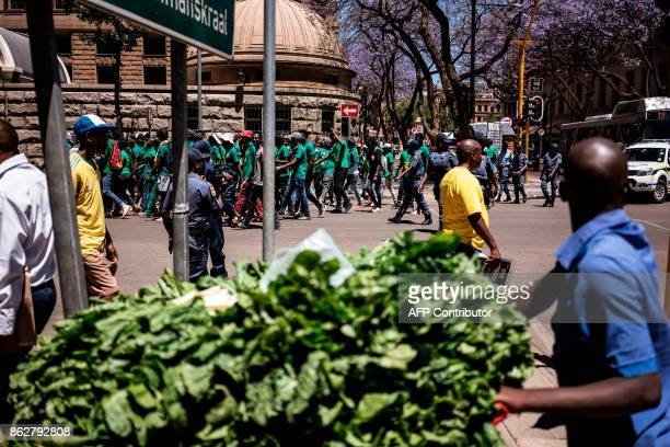 A hawker pushes a vegetable cart while passing by a demonstration by university students of the Pan African Student Movement of Azania in Pretoria on...