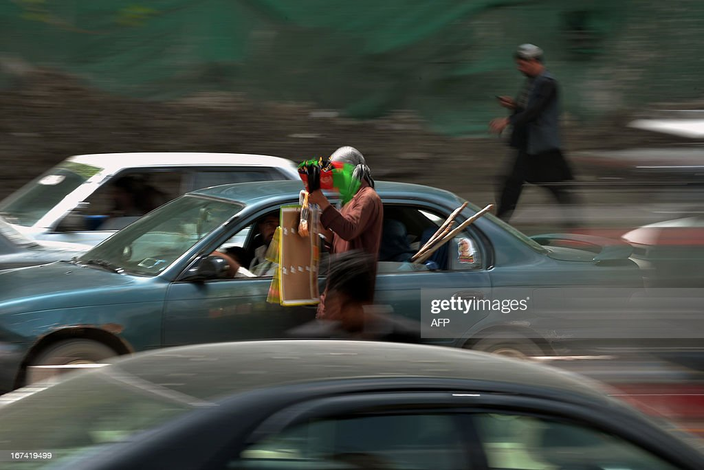 A hawker tries to sell the Afghan national flag at a busy traffic junction in Kabul on April 25, 2013. According to the report published by the Office of the High Commissioner for Human Rights (OHCHR), some 9 million Afghans – 36 per cent of the population – are believed to live in absolute poverty and a further 37 per cent live only slightly above the poverty line. AFP PHOTO/ Manjunath KIRAN