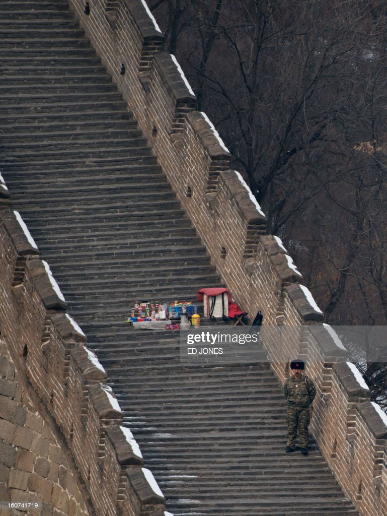 A hawker waits for customers beneath a watch tower on a quiet section of the Great Wall of China in Mutianyu, near Beijing on February 5, 2012. China is preparing to welcome the lunar new year, or spring festival, which falls on February 10. AFP PHOTO / Ed Jones