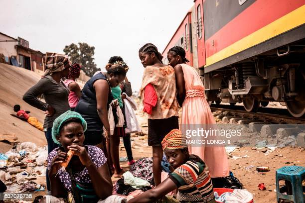 TOPSHOT Hawkers eat as they protect their goods as a freight train approaches in the Viana district in Luanda on August 22 2017 With current...