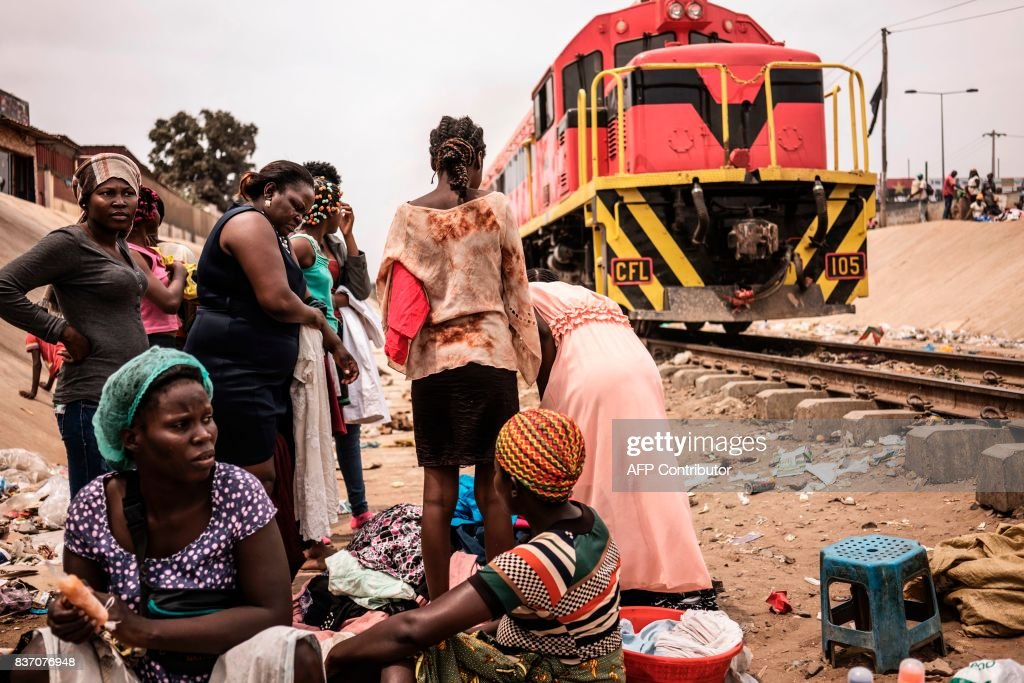Hawkers protect their goods as a freight train approaches in the Viana district in Luanda, on August 22, 2017. With current president Dos Santos standing down after the election, the ruling MPLA party -- which has held power since 1975 -- is expected to win again and install his chosen successor, Joao Lourenco, as head of state. /