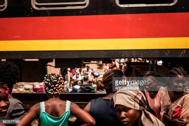 Hawkers protect their goods as a freight train approaches in the Viana district in Luanda on August 22 2017 With current president Dos Santos...