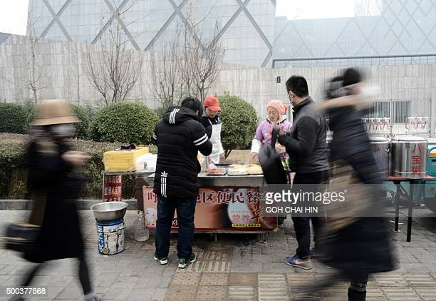 Hawkers sell pancakes to Chinese pedestrians along a street near the Chinese Central Television building on a heavily polluted day in Beijing on...