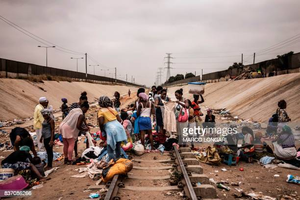 TOPSHOT Hawkers sell their products in an improvised market across a train track in the Viana district in Luanda on August 22 2017 With current...