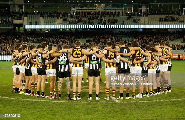 Hawks and Magpies players form a circle in remembrance of Phil Walsh after the 2015 AFL round 14 match between the Collingwood Magpies and the...