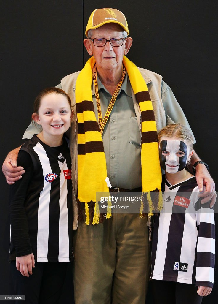 A Hawks fan shows his support along with his two grand children who support the Magpies during the round three AFL match between the Collingwood Magpies and the Hawthorn Hawks at Melbourne Cricket Ground on April 14, 2013 in Melbourne, Australia.