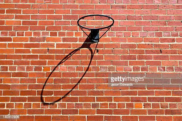A basketball hoop casts a long shadow on a red brick wall.