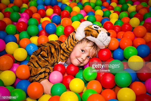 A small boy dressed as a tiger playing in a pool of colorful balls.