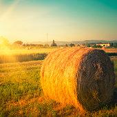 Hay bail on pring field at dusk