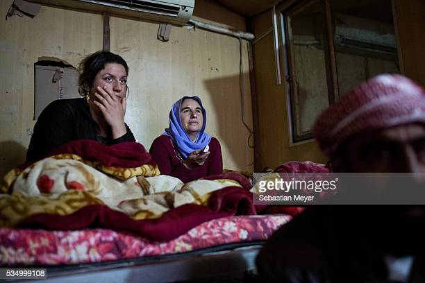 Hayam Ghazal and Said watch television in the shipping container they call home A family of displaced Yezidis lives next to an oil refinery in the...