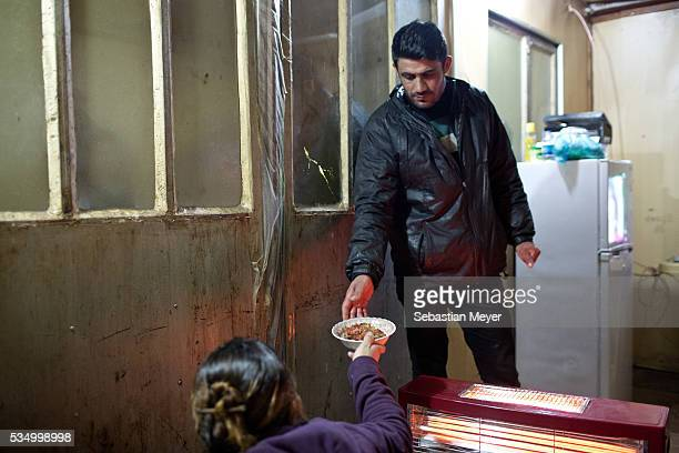 Hayam hands Serbest his dinner before he heads over the refinery The family of Yezidis displaced from Sinjar live next to an oil refinery in the...