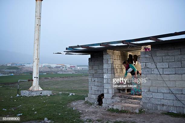 Hayam takes a plastic bowl to wash vegetables for dinner The family of Yezidis displaced from Sinjar live next to an oil refinery in the Kurdish...