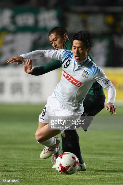 Hayato Nakama of Kamatamare Sanuki is challenged by Yudai Iwama of Matsumoto Yamaga during the JLeague J2 match between Matsumoto Yamaga and...