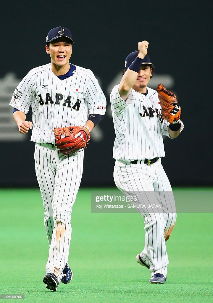 Hayato Sakamoto (L) #6 and Nobuhiro Matsuda (R) #3 of Japan celebrate their team's 5-0 win in the WBSC Premier 12 match between Japan and South Korea at the Sapporo Dome on November 8, 2015 in Sapporo, Japan.