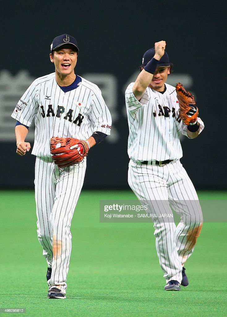 Hayato Sakamoto and Nobuhiro Matsuda of Japan celebrate their team's 50 win in the WBSC Premier 12 match between Japan and South Korea at the Sapporo...