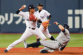 Hayato Sakamoto of Samurai Japan turns a double play as Evan Longoria of the Tampa Bay Rays slides into second base in the sixth inning during the...
