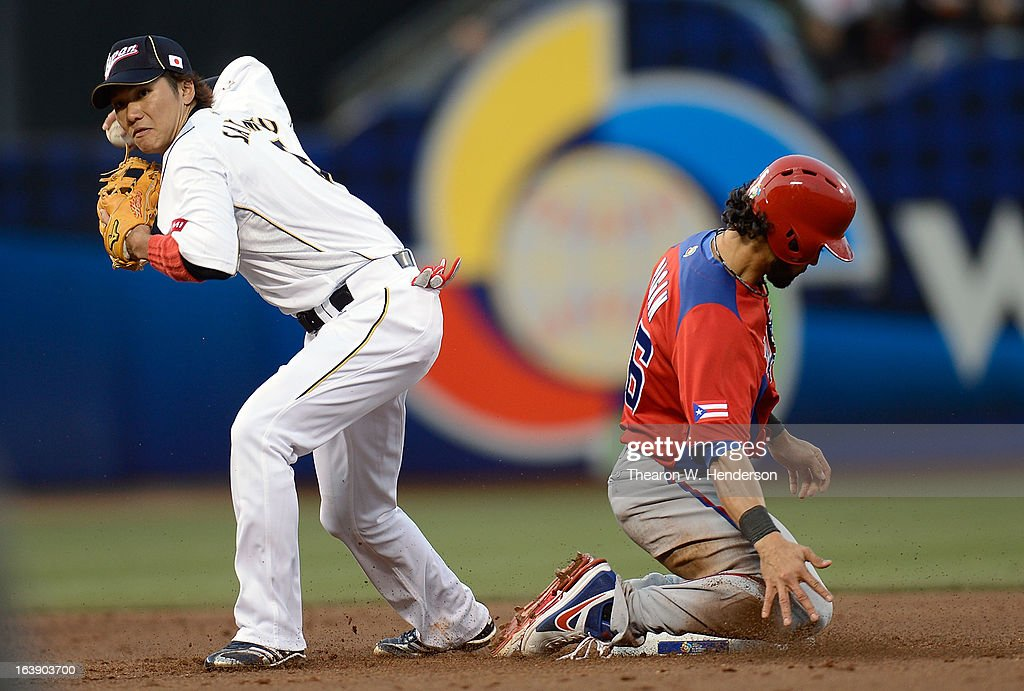 Hayato Sakamoto #6 of Team Japan, to get his throw off for a double play, steps to the side of a sliding Angel Pagan #16 of Team Puerto Rico in the third inning during the World Baseball Classic Semifinals at AT&T Park on March 17, 2013 in San Francisco, California.