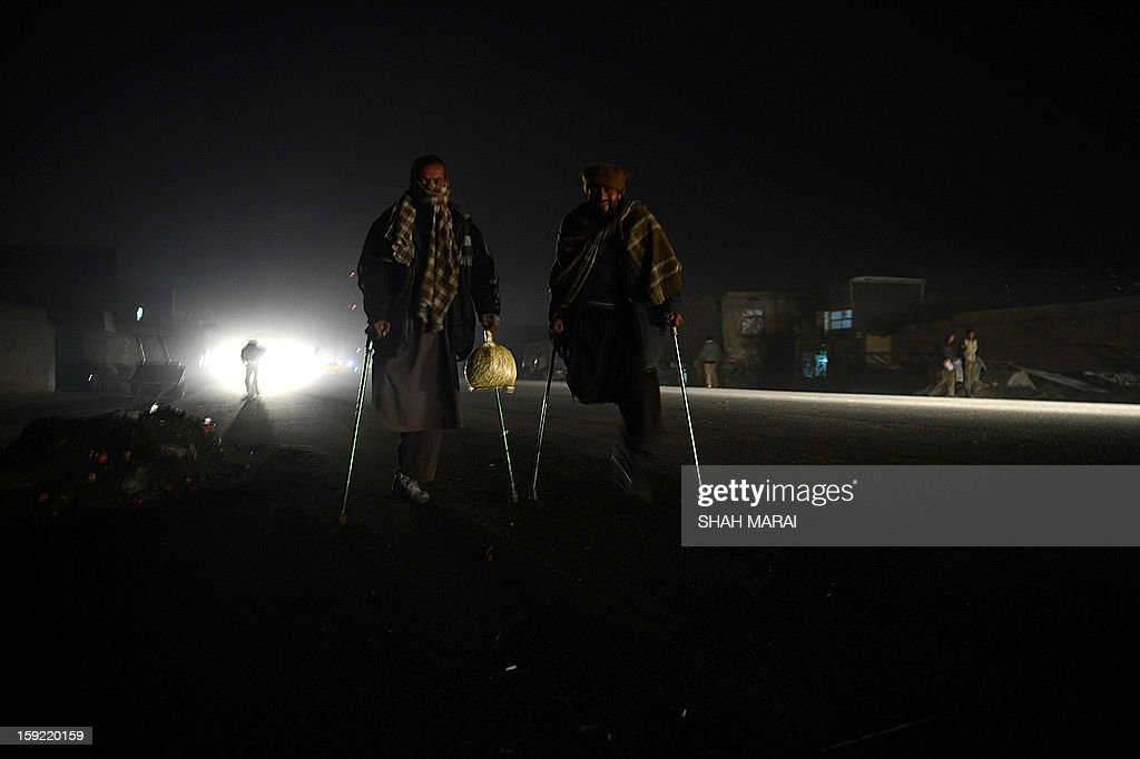 Hayatullah, 35, (L) who like most Afghans goes by only one name carries a bag of cooked rice left over from customers in a Kabul restaurant and Merzamullah ,35, walk in Kabul late on January 9, 2013. Hayatuallah lost a leg to a land mine in Shamali plain, north of Kabul during the deadly Afghan civil war of 1991-1996. Afghanistan is still one of the heavily mined countries in the world despite international efforts to clean the poverty-nation from millions of mines that were planted by the former Soviet ary between 1979 and 1987, followed by a deadly civil war between Afghan faction that defeated the Russian and Taliban who rulled the troubled country between 1996 and 2001 and now waging an insurgency against the NATO forces and use roadside bombings, improvised explosives devices as a main weapon in their war tactics. AFP PHOTO/ SHAH Marai