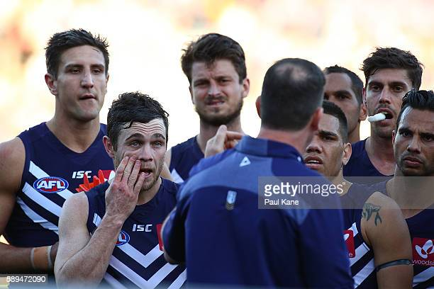 Hayden Ballantyne of the Dockers looks on as Dockers head coach Ross Lyon addresses the team at the three quarter time break during the round 21 AFL...