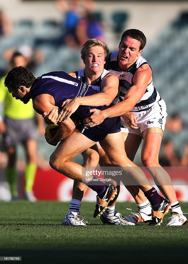 Hayden Ballantyne of the Fremantle Dockers is tackled by Josh Caddy of the Geelong Cats during the round one NAB Cup AFL match between the Fremantle Dockers and the Geelong Cats at Patersons Stadium on February 16, 2013 in Perth, Australia.