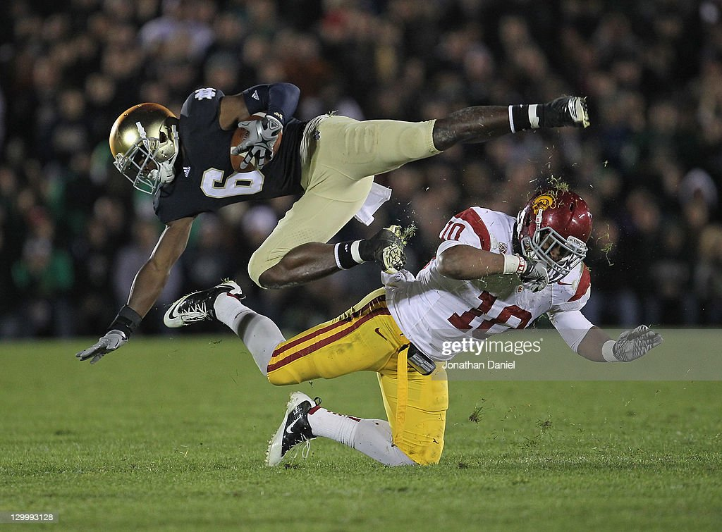 Hayes Pullard #10 of the University of Southern California Trojans upends <a gi-track='captionPersonalityLinkClicked' href=/galleries/search?phrase=Theo+Riddick&family=editorial&specificpeople=6235084 ng-click='$event.stopPropagation()'>Theo Riddick</a> #6 of the Notre Dame Fighting Irish at Notre Dame Stadium on October 22, 2011 in South Bend, Indiana. USC defeated Notre Dame 31-17.