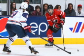 Hayley Wickenheiser of Team Canada looks to pass around Megan Bozek of Team USA during a Sochi Olympics preparation game at the Air Canada Centre...