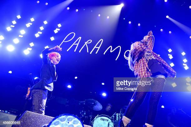 Hayley Williams of Paramore performs onstage with a fan during KISS 108's Jingle Ball 2013 at TD Garden on December 14 2013 in Boston MA