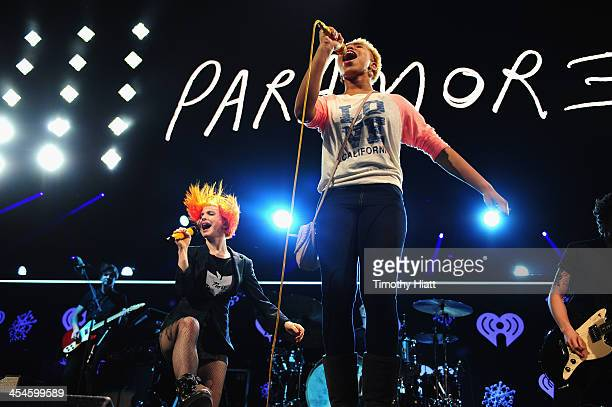 Hayley Williams of Paramore performs with a fan onstage during 1035 KISS FM's Jingle Ball 2013 presented by Jam Audio Collection at United Center on...