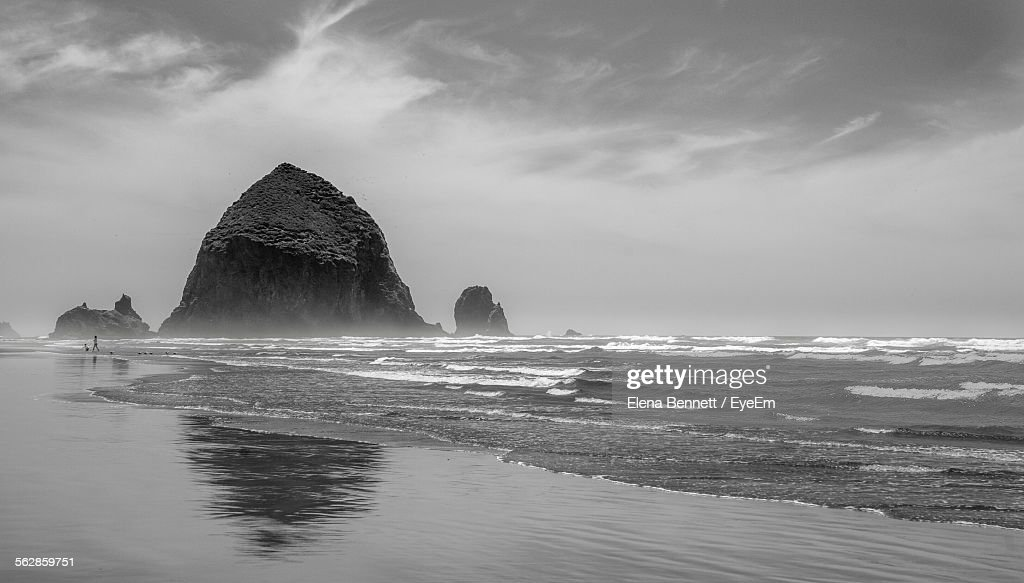 Haystack Rock Formations At Cannon Beach Against Cloudy Sky