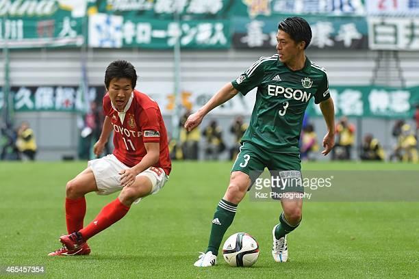 Hayuma Tanaka of Matsumoto Yamaga keeps the ball under the pressure from Kensuke Nagai of Nagoya Grampus during the J League match between Nagoya...