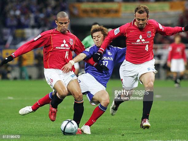 Hayuma Tanaka of Yokohama FMarinos competes for the ball against Alessandro Santos and Marcus Tulio Tanaka of Urawa Red Diamonds during the JLeague...