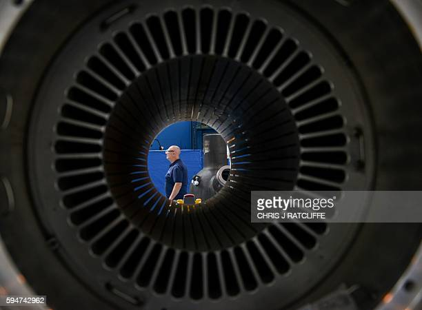 A Hayward Tyler employee is seen through a winding engine on the factory floor at the Hayward Tyler manufacturing facility in Luton north of London...