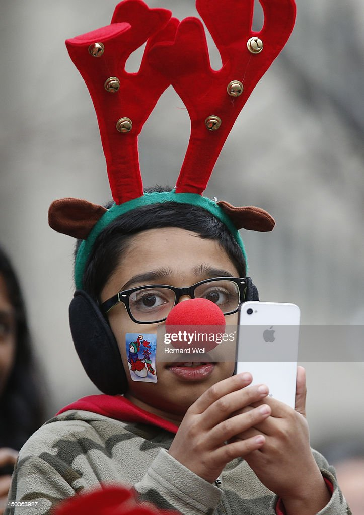 Hayyan Shariff, 10, of Toronto, gets photos of the approaching parade during the 109th annual Santa Claus Parade, Toronto. November 17, 2013.