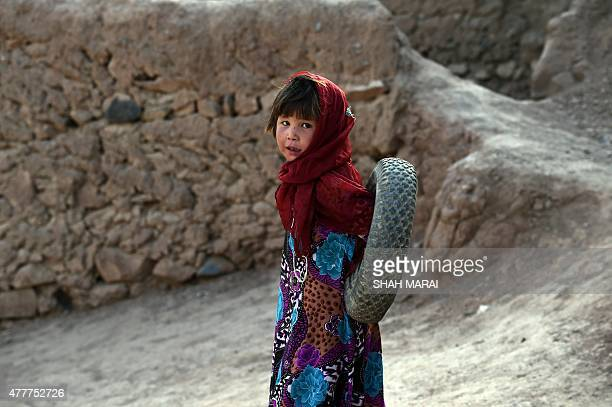 A Hazara Afghan girl plays with a tire in the old city of Bamiyan on July 19 2015 Bamiyan some 200 kilometres northwest of Kabul stands in a deep...