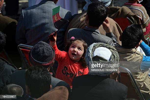 A Hazara ethnic girl holds an Afghanistan flag at the Sakhi shrine the centre of the Afghanistan new year celebrations in Kabul during Nowruz...