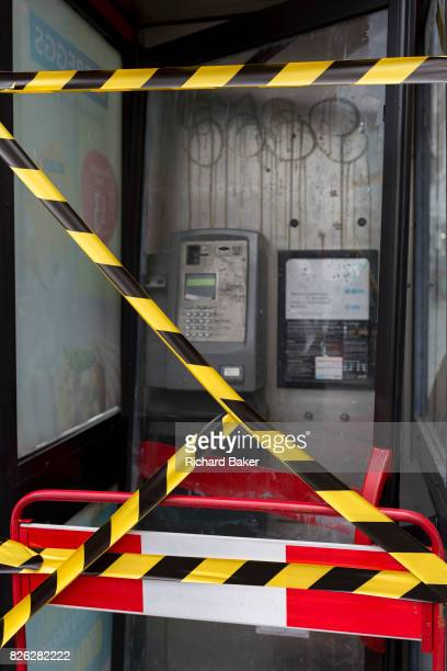 Hazard tape stretched across the glass of an old telephone kiosk on Tottenham Court Road on 3rd August 2017 in London England