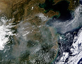 October 2, 2009 - Gray-white haze blankets patches of the North China Plain and the mountain landscape to its south in this satellite image. The haze flows out of China in an arcing ribbon that stretc