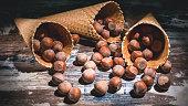 Hazelnut nuts in waffle cones on a dark background. Low key lighting.