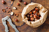 Hazelnuts, organic healthy snack and vintage nutcracker on wooden background, top view