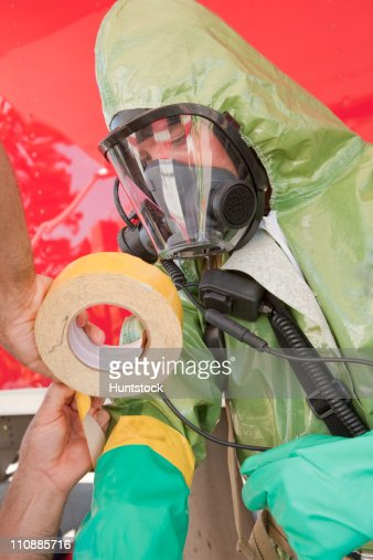 HazMat firefighter assisting his colleague in taping protective gloves