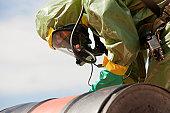 HazMat firefighter examining a chemical drum