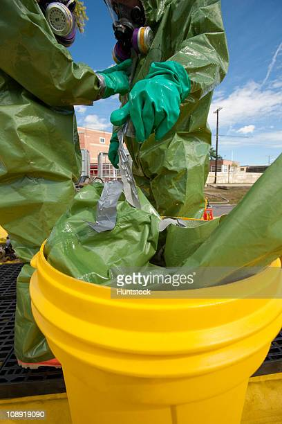 HazMat firefighter getting decontamination wash and discarding clothing