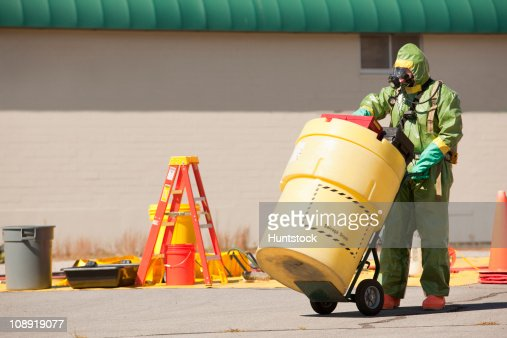 HazMat firefighter pushing a salvage drum : Stock-Foto