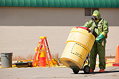 HazMat firefighter pushing a salvage drum
