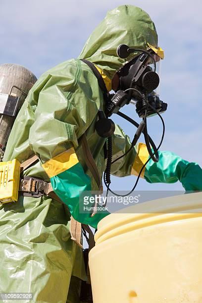 HazMat firefighter pushing a salvage drum